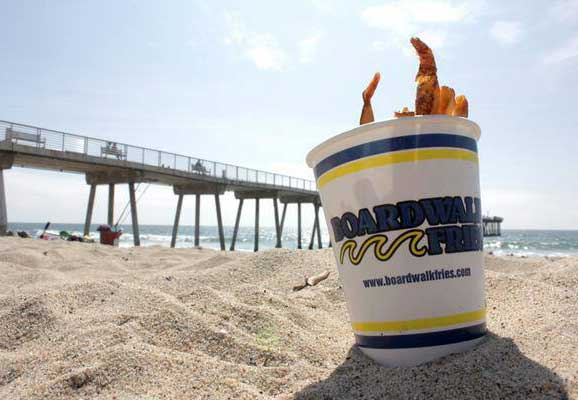 A bucket of fries on the beach.